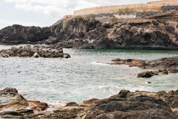 Long shot costa de penhasco com água cristalina Foto gratuita