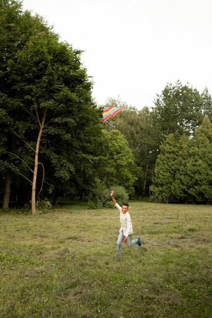Long shot de menino feliz se divertindo com uma pipa Foto gratuita