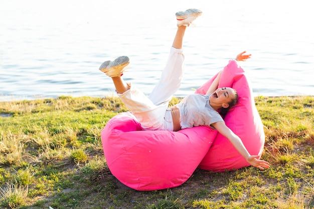 Long shot mulher despreocupada posando em um pufe rosa Foto gratuita