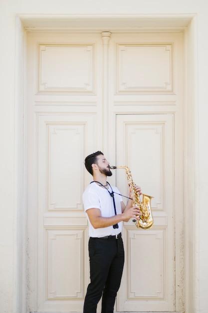 Long shot músico lateralmente tocando saxofone Foto gratuita