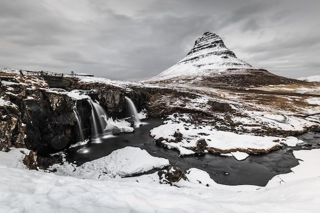 Longa exposição da montanha com primeiro plano de cachoeira no inverno Foto Premium