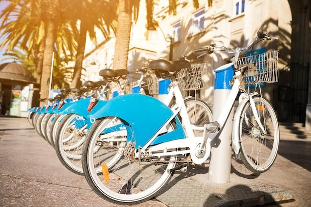 Longa fila de bicicletas para alugar estacionado em uma rua Foto gratuita