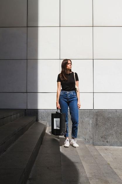Longo tiro moda mulher posando com uma sacola de compras Foto gratuita