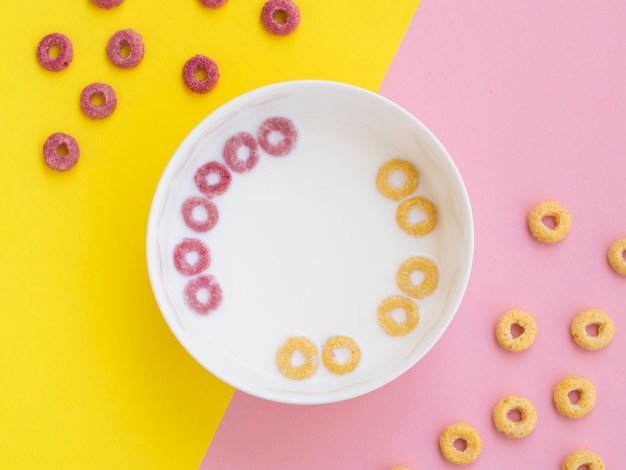 Loops de cereal de frutas-de-rosa e amarelas em uma tigela Foto gratuita