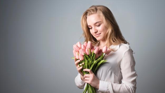 Louro encantador que aprecia o grupo de flores Foto gratuita