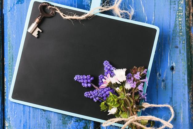 Lousa com flores e chave Foto Premium