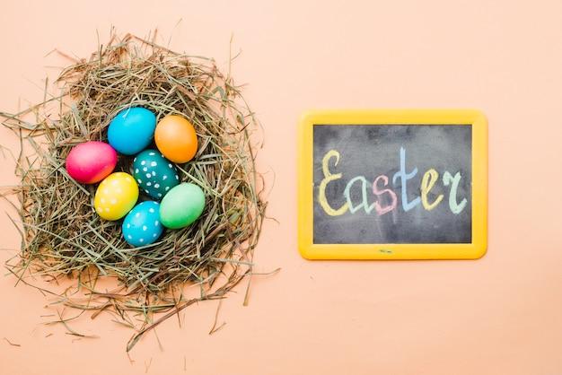 Lousa com o título de páscoa perto de conjunto de ovos coloridos brilhantes no ninho Foto gratuita