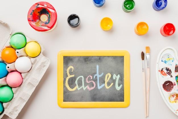 Lousa com o título de páscoa perto de ovos coloridos no recipiente, pincéis, cores de água e paleta Foto gratuita