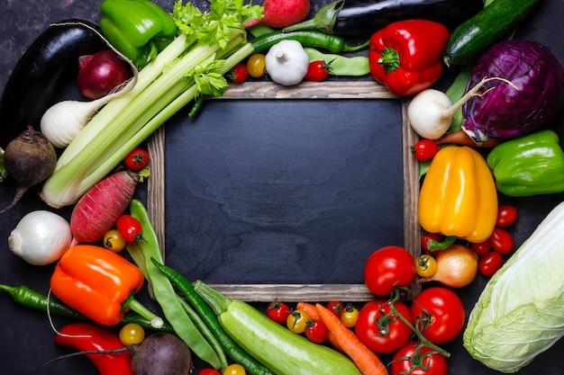 Lousa com vegetais saudáveis coloridos diferentes em fundo escuro Foto gratuita