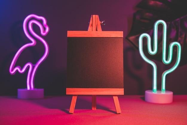 Lousa de verão com flamingo e cacto néon rosa e azul luz na mesa Foto Premium