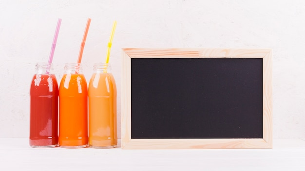 Lousa e garrafas de suco colorido Foto gratuita