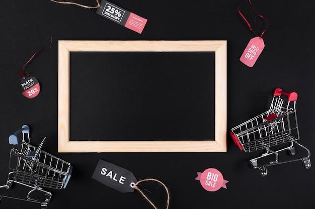 Lousa em branco com carrinhos de compras do lado Foto gratuita
