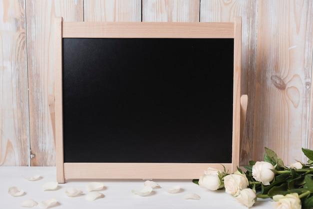 Lousa em branco com lindas rosas na mesa de madeira branca Foto gratuita
