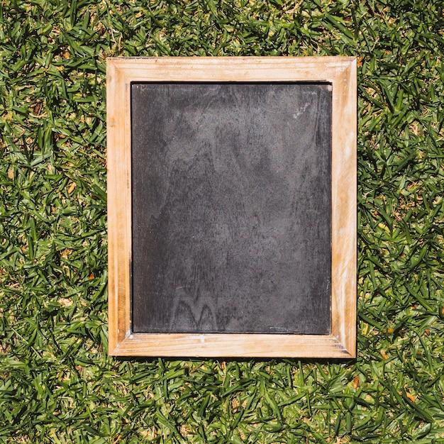 Lousa vazia com molduras de madeira sobre fundo verde Foto gratuita