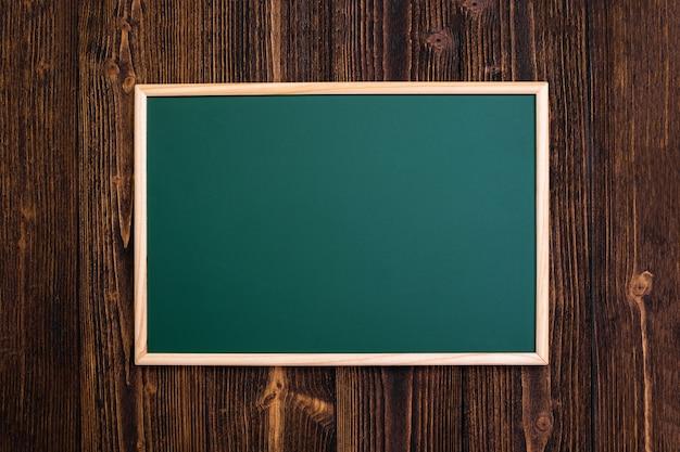 Lousa verde vazia com moldura de madeira na mesa de madeira Foto Premium