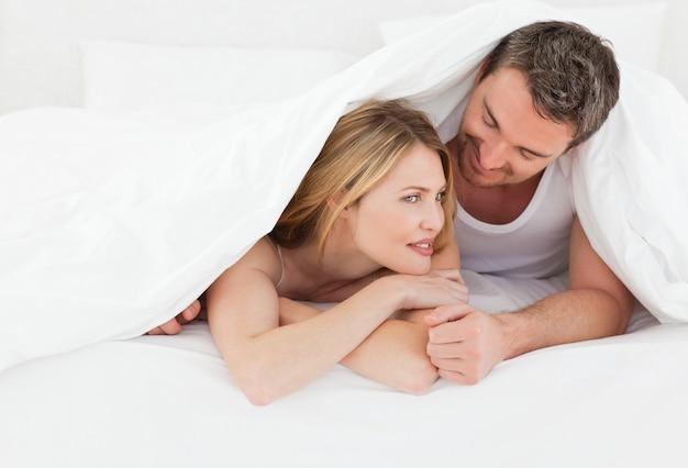 Lovely par abraçando na cama Foto Premium