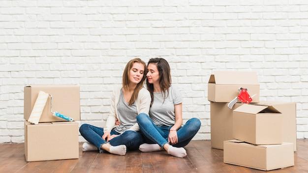 Loving casal jovem lésbica sentado no chão de madeira com caixas de papelão em movimento em sua nova casa Foto gratuita