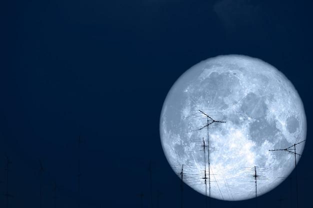 Lua cheia de leite volta em antenas de silhueta no céu noturno Foto Premium
