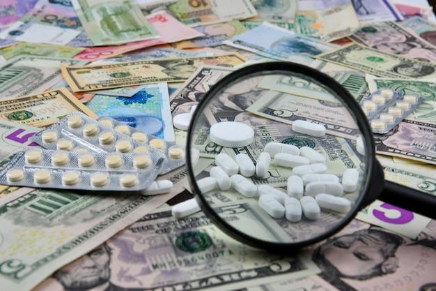 Lupa, comprimidos e termômetro em notas de moeda de diferentes países. a disponibilidade médica e o aumento das despesas médicas. Foto Premium