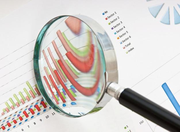 Lupa e o documento de trabalho com um diagrama Foto Premium