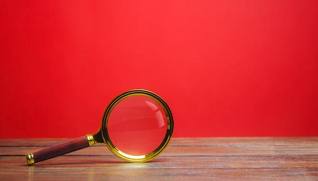 Lupa sobre um fundo vermelho. pesquisa e análise, análise e estudo. Foto Premium