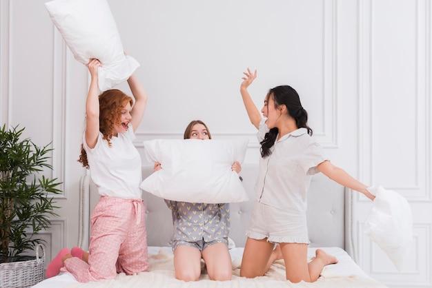 Luta de almofadas na festa do pijama Foto gratuita