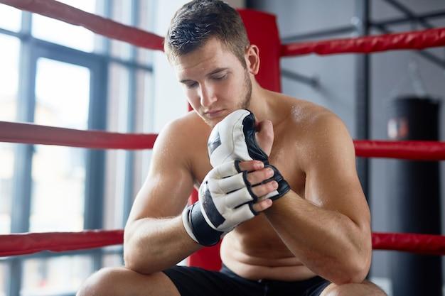 Lutador em repouso no ringue de boxe Foto gratuita