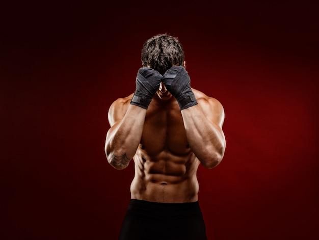 Lutador muscular forte, escondendo o rosto da câmera Foto Premium