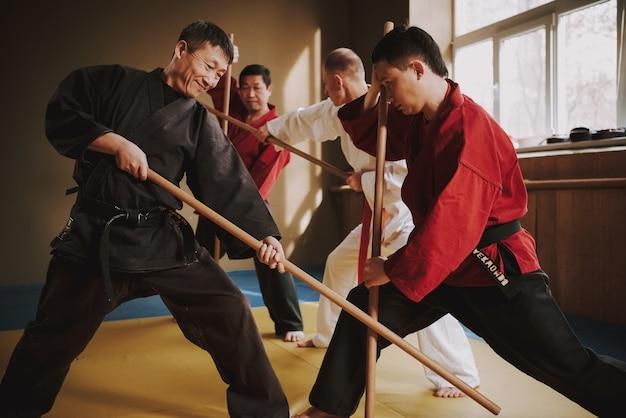 Lutadores de artes marciais de karatê lutando com paus Foto Premium