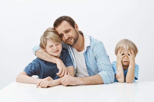 Luto do pai com os filhos enquanto está sentado à mesa, abraçando o menino e chorando, ficando chateado e infeliz enquanto o filho mais novo não tem nada para fazer Foto gratuita