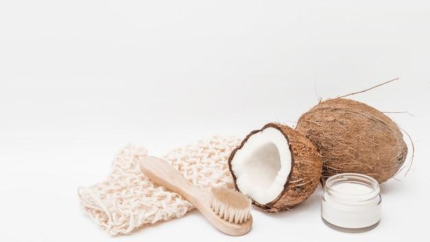 Luva macia; escova; coco e creme hidratante no fundo branco Foto gratuita