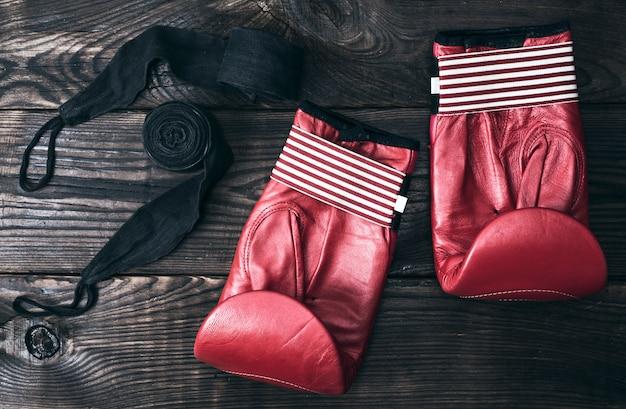 Luvas de boxe de couro vermelho e uma atadura elástica preta Foto Premium