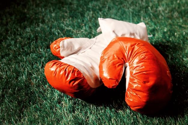 Luvas de boxe vermelhas na grama verde. Foto Premium
