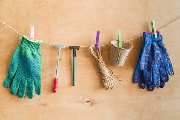 Luvas de jardinagem; ferramentas; corda; potes de turfa pendurado na corda com pregador contra a parede de madeira Foto gratuita