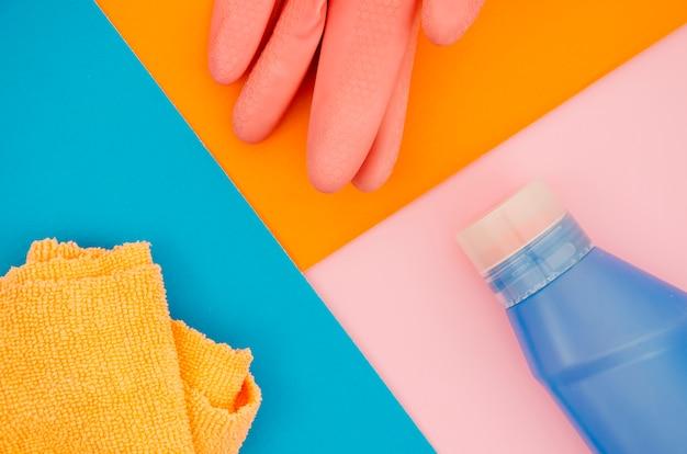 Luvas; guardanapo e garrafa em uma laranja; fundo azul e rosa Foto gratuita