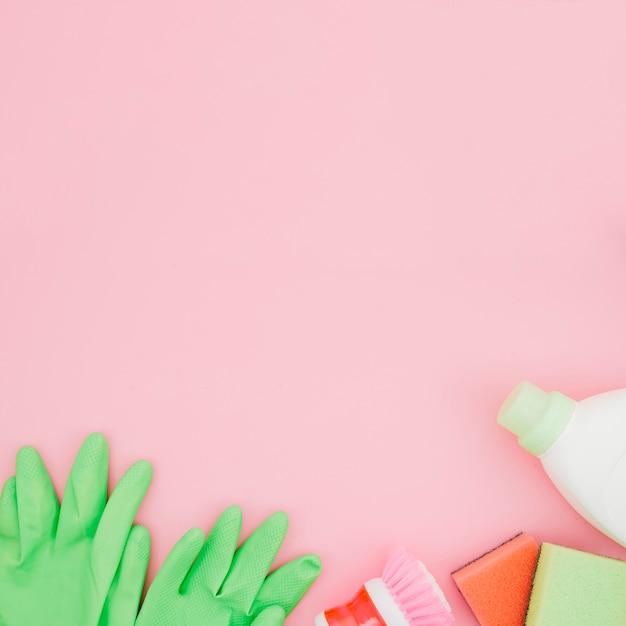 Luvas verdes; garrafa de spray; garrafas de esponja e detergente em pano de fundo amarelo Foto gratuita