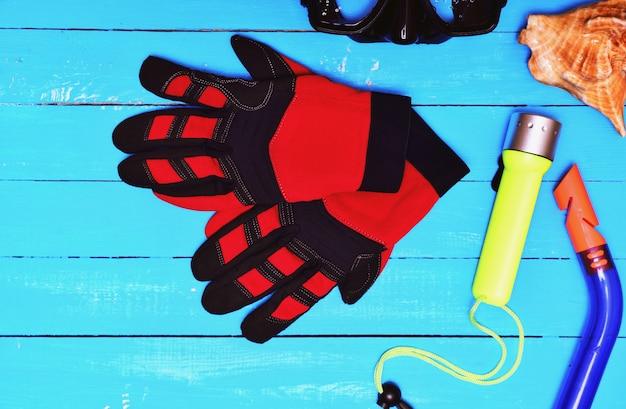 Luvas vermelhas para mergulho entre outros equipamentos esportivos Foto Premium
