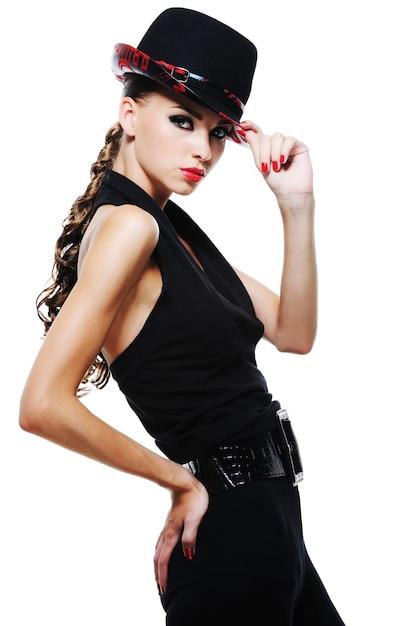 Luxo glamour elegante garota adulta em um vestido preto com um chapéu preto estiloso Foto gratuita