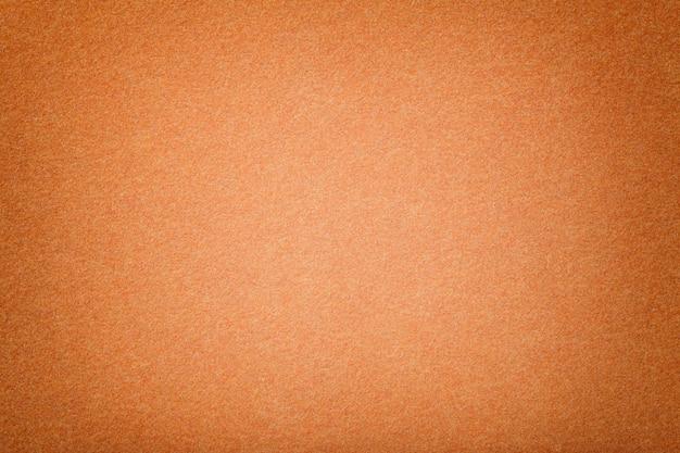 Luz - close up matt alaranjado da tela da camurça. textura de veludo de feltro. Foto Premium