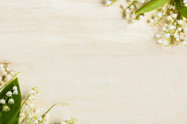 Luz de fundo de madeira. flores lírios do vale. Foto Premium