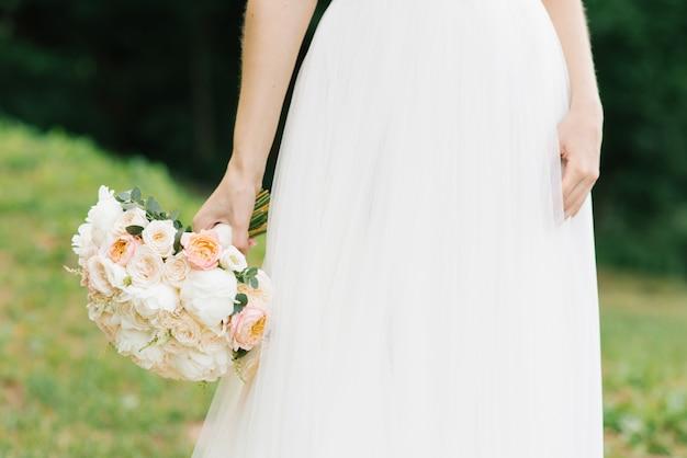 Luz delicado buquê da noiva nas mãos da noiva Foto Premium