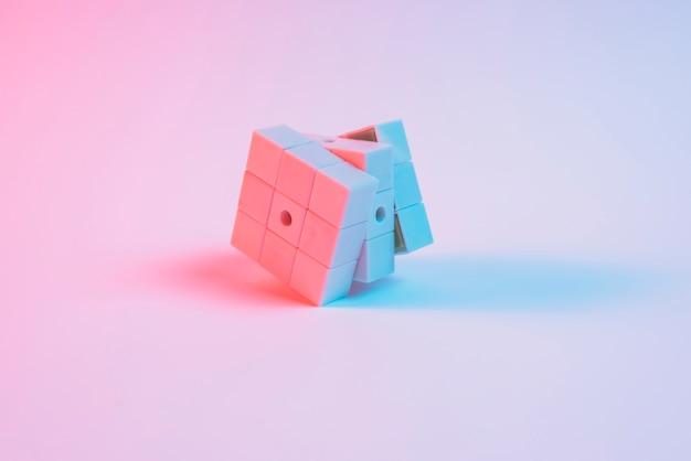 Luz do ponto azul sobre o cubo de rubik rosa no fundo liso Foto gratuita