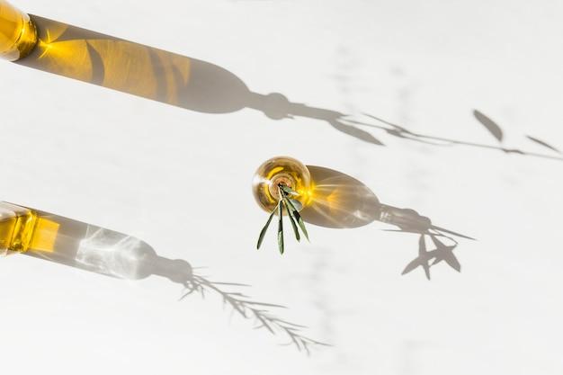 Luz do sol caindo sobre as garrafas de azeite no pano de fundo branco Foto gratuita