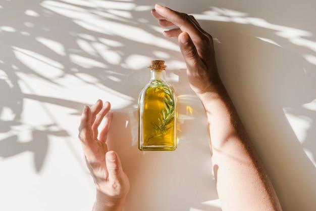 Luz do sol caindo sobre as mãos cobrindo a garrafa de óleo no fundo branco Foto gratuita