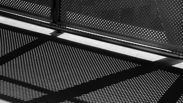 Luz e sombra de malha de arame no pavimento - monocromático Foto Premium