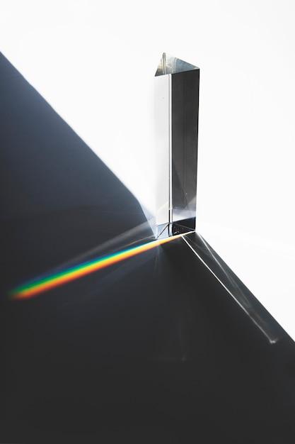 Luz que passa através de um prisma triangular com sombra escura na superfície branca Foto gratuita