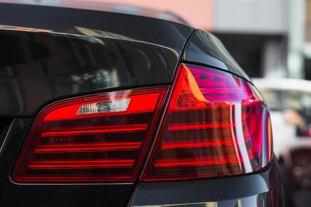 Luz traseira no novo carro preto na rua Foto gratuita