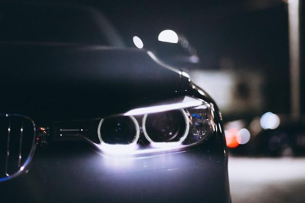 Luzes da frente do carro à noite na estrada Foto gratuita