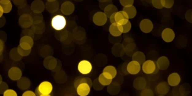 Luzes de natal douradas desfocadas em fundo escuro. círculos amarelos bokeh em fundo preto, fundo de natal Foto Premium