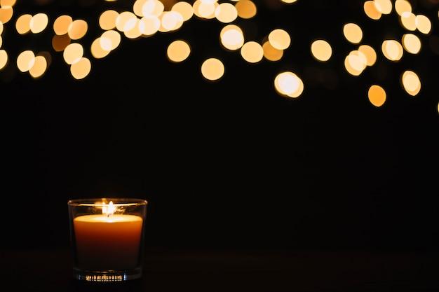Luzes desfocadas sobre vela Foto gratuita